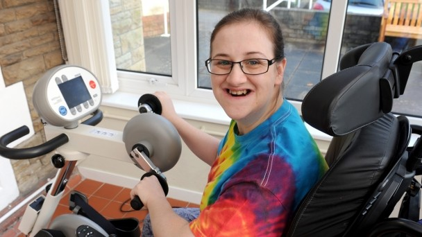 Laura using a specially adapted exercise bike with a big smile on her face
