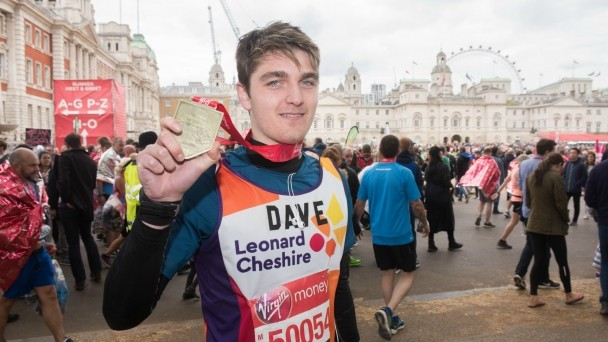 London Marathon runner Dave holding his medal at the finisher line