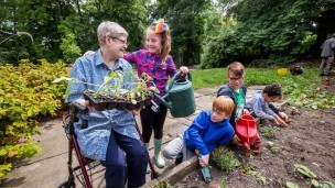 A young girl helps an older woman with the gardening