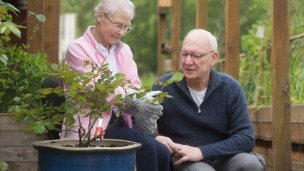 Two people, a man and a woman, plant a rose in memory of Kay