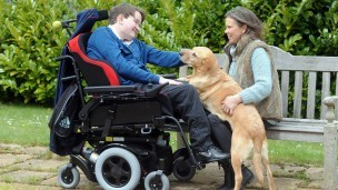 Tom in his wheelchair with his mum and a guide dog
