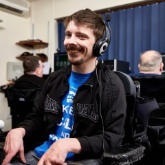 Smiling man is sitting in a computer room and wearing headphones