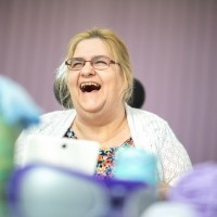 A woman wearing glasses laughs